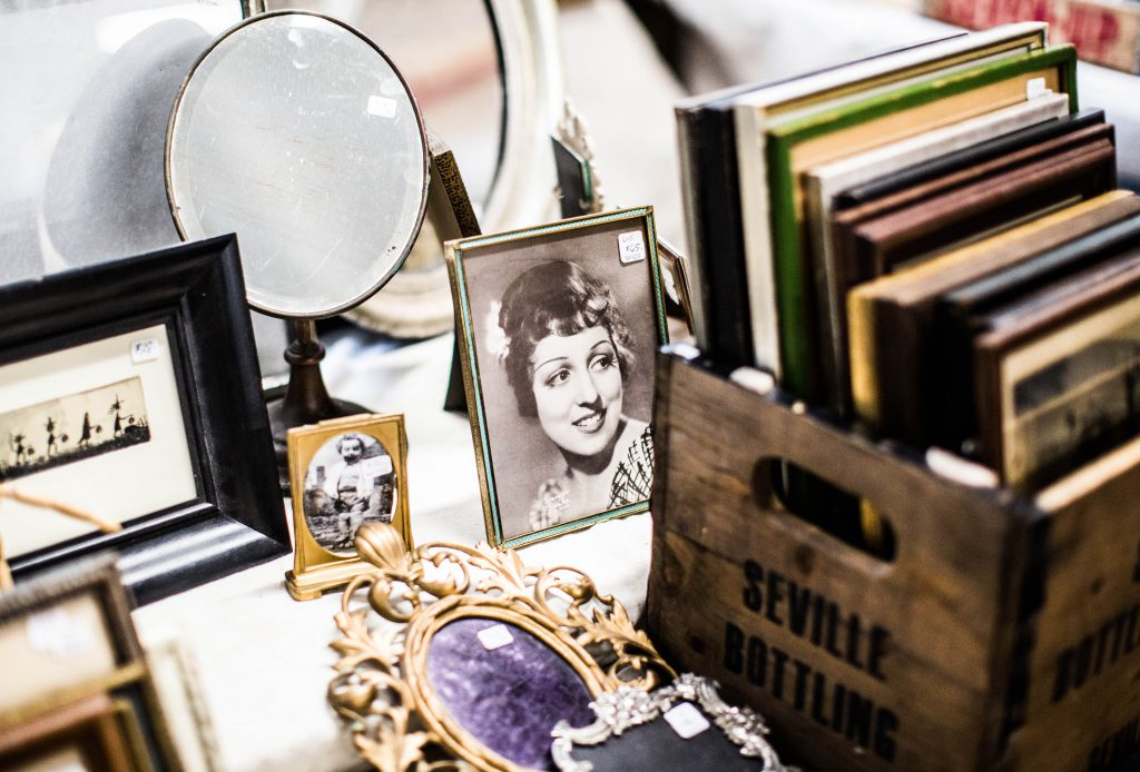 vintage family photos in frames on desk next to crate full of picture frames