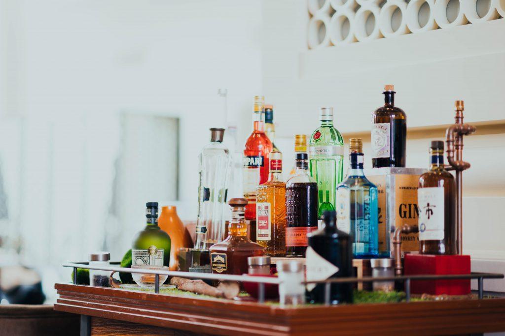 home bar cart with various liquor bottles