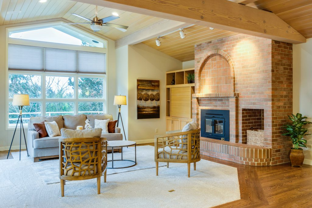 brick fireplace in living room with vaulted ceilings