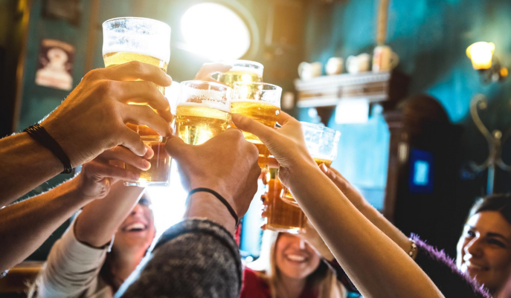 group at a brewery raising their glasses in a toast