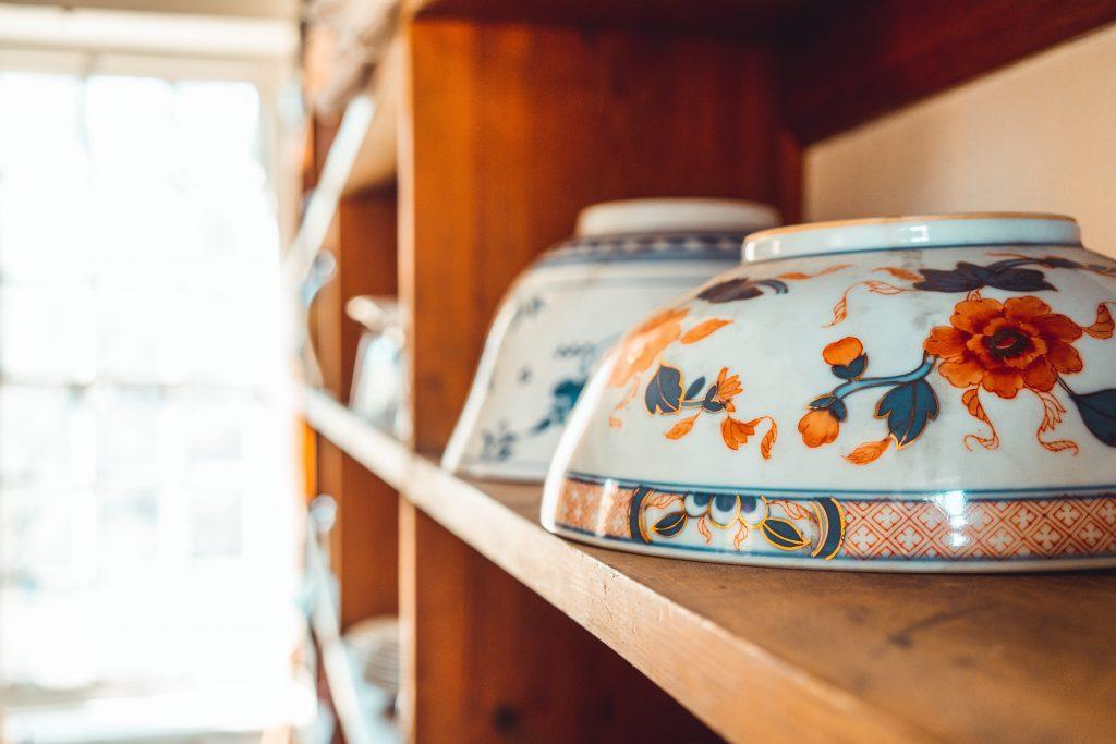 porcelain bowls with floral print turned upside down on shelf