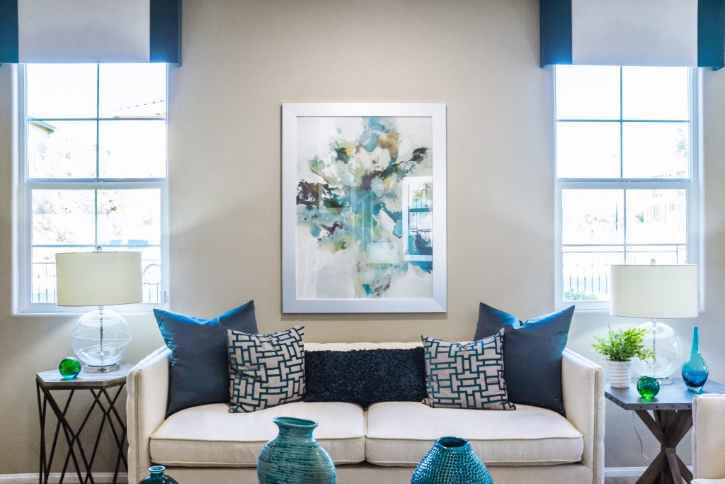 couch between two windows with art hanging above pillows