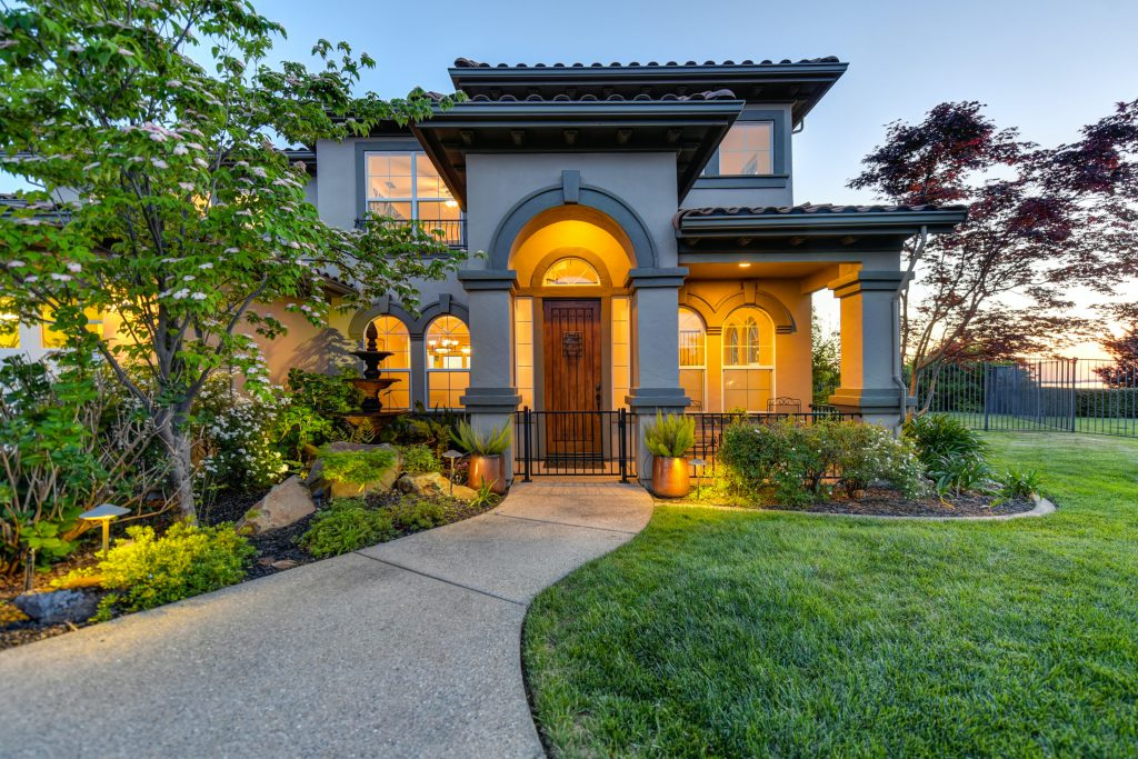 beautiful home for sale with lights on early evening arched portico wooden door