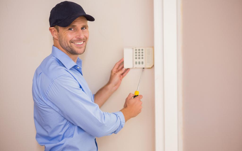 handyman fixing thermostat