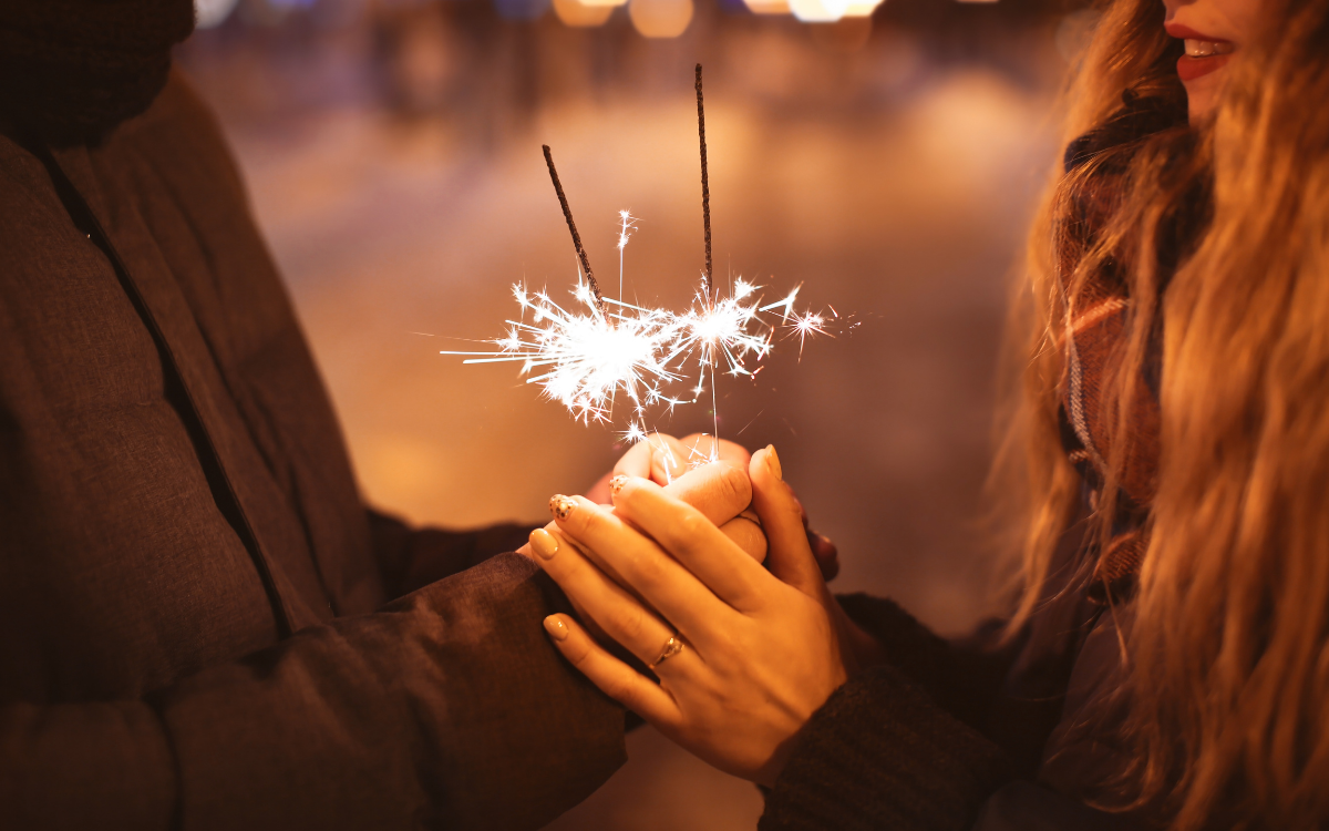 couple holding hands with sparklers between them
