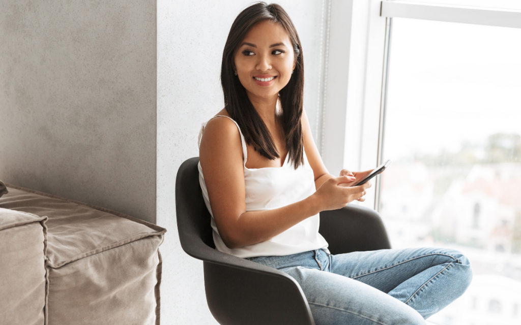 young asian woman sitting in chair holding phone in apartment