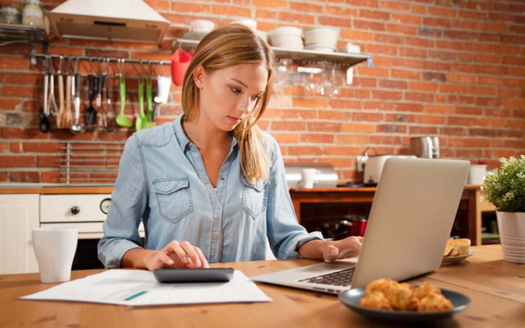 young woman planning budget on laptop