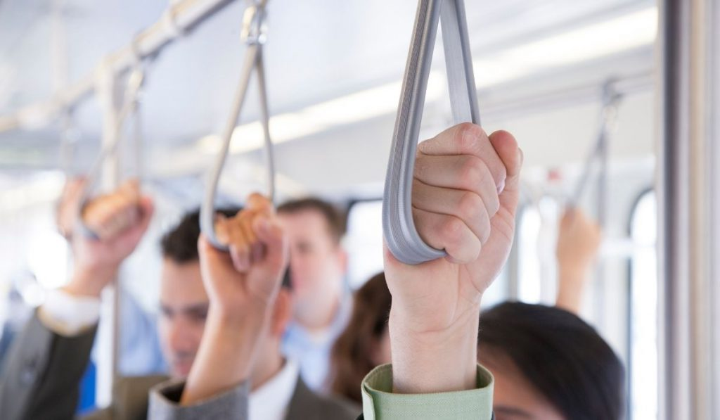 commuters in the bus holding the hanging strap on their way to work