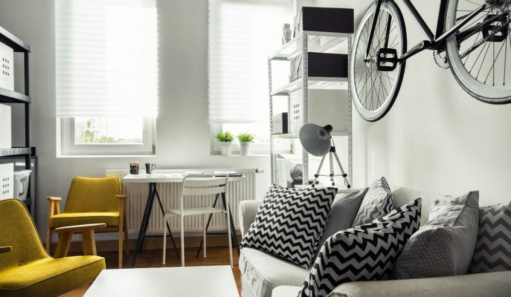micro apartment with a bike hanging on the wall; black and white colors